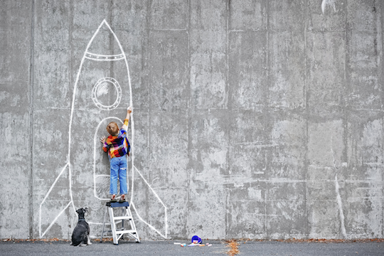 boy drawing rocketship with chalk on concrete wall