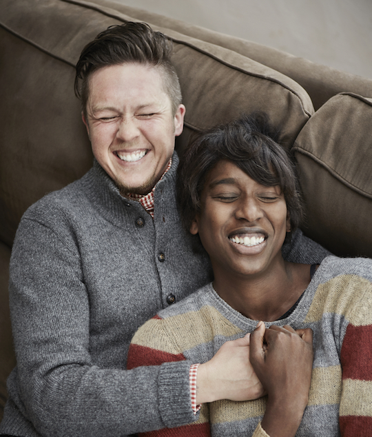 Transgender man and wife laughing on the couch