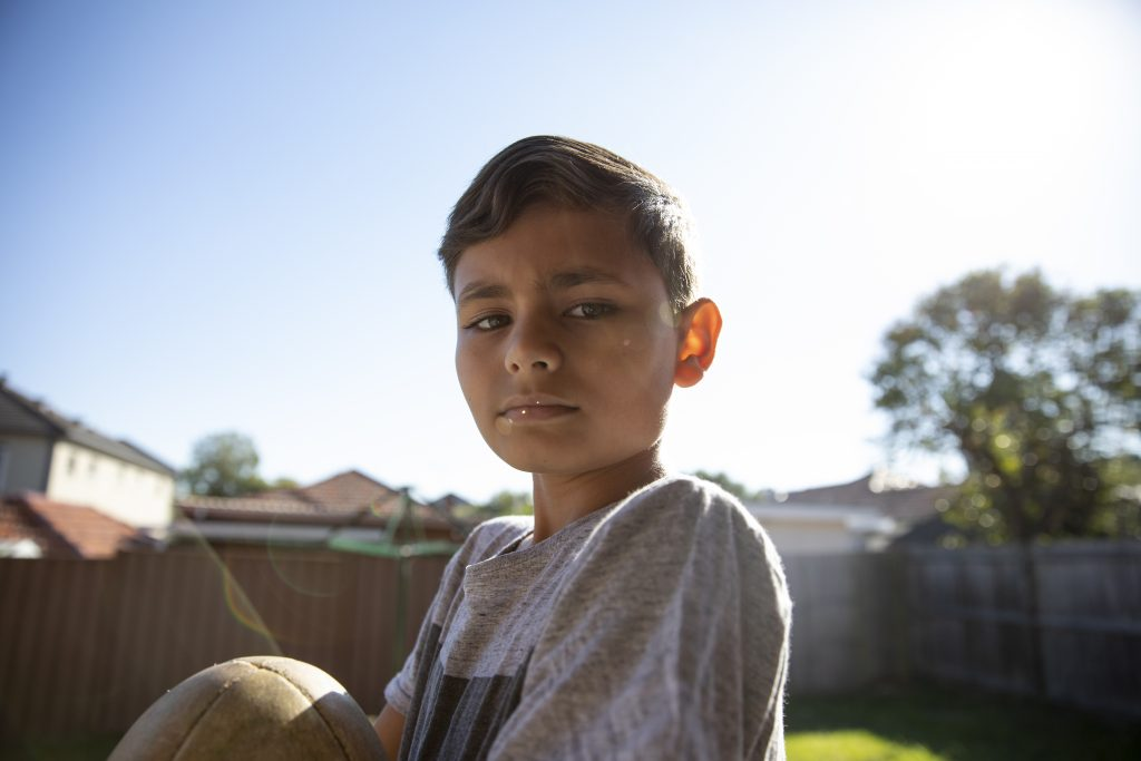 Portrait of Indigenous Australian aboriginal boy holding rugby ball